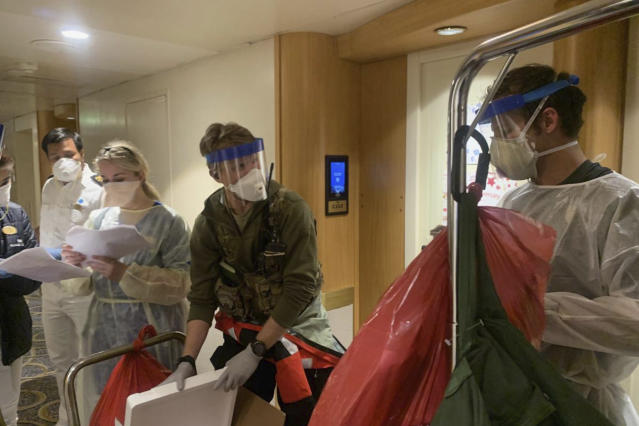 Medical personnel checking passengers on the ship this week. (AP)