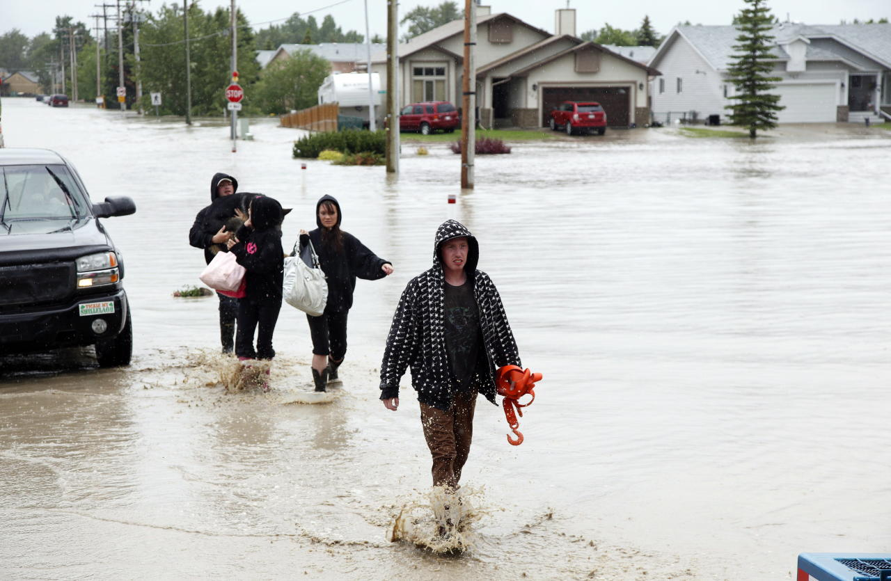 Residents wade through flood waters after an evacuation order following heavy rains caused flooding, closed roads, and forced evacuation in High River, Alta., Thursday, June 20, 2013.