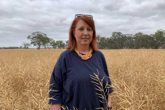 A woman with red hair, blue shirt and orange necklace stands in a canola crop that's ready to harvest.