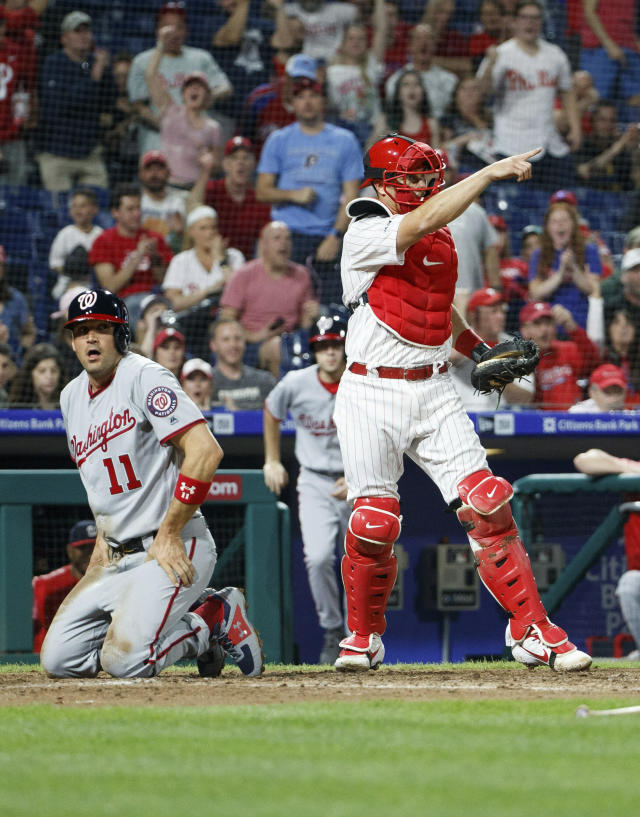 Philadelphia Phillies' J.T. Realmuto, right, reacts after tagging out Washington Nationals' Ryan Zimmerman, left, during the fourth inning of a baseball game, Monday, April 8, 2019, in Philadelphia. (AP Photo/Chris Szagola)