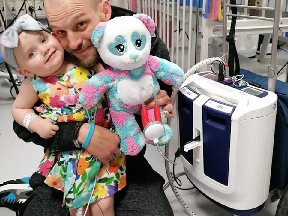 Baby Grace with father Darren and her new portable heart pump (PA)