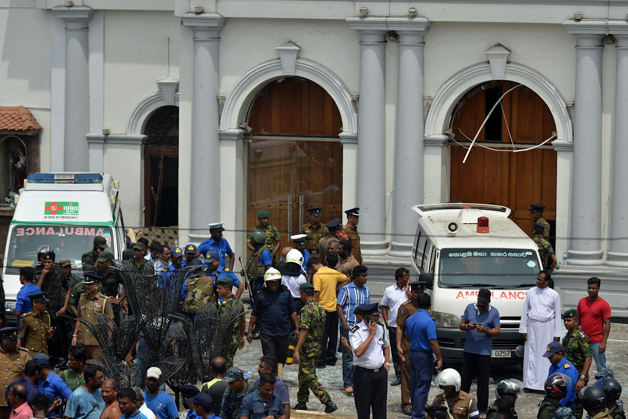 Ambulances are seen outside the church premises with gathered people and security personnel following a blast at the St. Anthony's Shrine in Kochchikade, Colombo (GETTY)