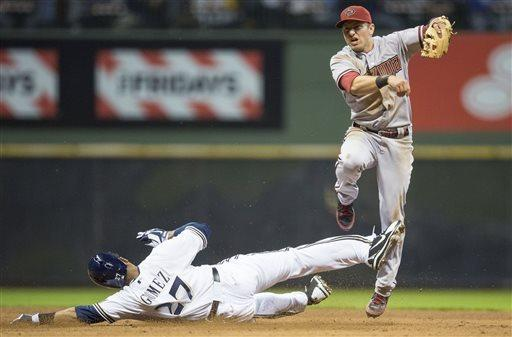 Milwaukee Brewers' Carlos Gomez is forced out at second base as Arizona Diamondbacks' Cliff Pennington turns a double play during the sixth inning of a baseball game Saturday, April 6, 2013, in Milwaukee. Khris Davis was out at first. (AP Photo/Tom Lynn)