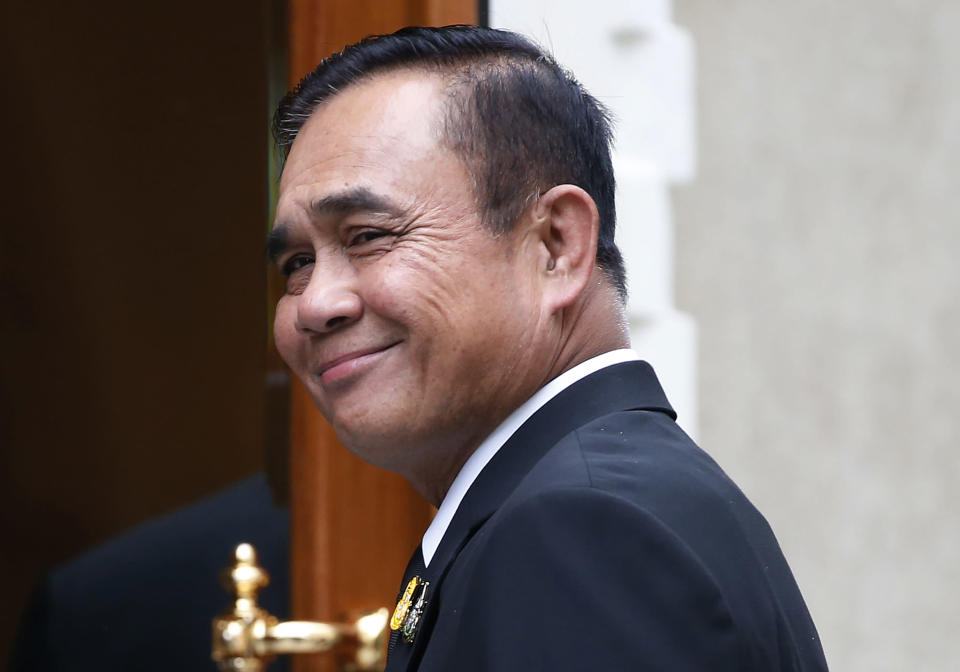Thailand's Prime Minister Prayuth Chan-ocha smiles as he talks reporters before meeting at government house in Bangkok, Thailand, Thursday, June 6, 2019. Thailand's Parliament elected 2014 coup leader Prayuth Chan-ocha as prime minister in a vote Wednesday that helps ensure the military's sustained dominance of politics since the country became a constitutional monarchy nearly nine decades ago. (AP Photo/Sakchai Lalit)