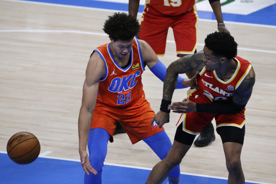 Atlanta Hawks forward John Collins (20) passes the ball away from Oklahoma City Thunder center Isaiah Roby (22) during the first half of an NBA basketball game Friday, Feb. 26, 2021, in Oklahoma City. (AP Photo/Garett Fisbeck)