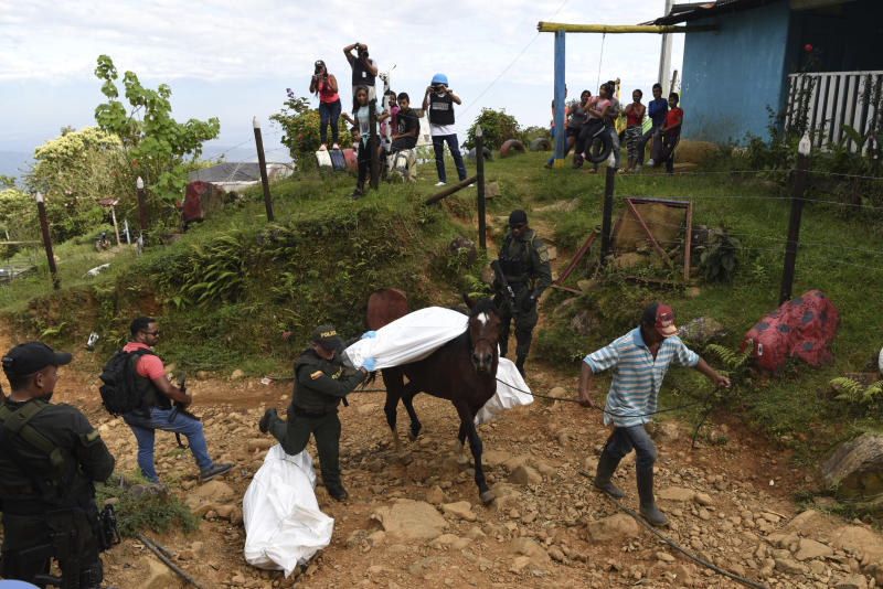 A police officer helps transport the body of one of at least five people killed during a skirmish between illegal armed groups in Jamundi in southwest Colombia, Friday, Jan. 17, 2020. Authorities say rebels with the former Revolutionary Armed Forces of Colombia operate in the area and may have been involved. (AP Photo/Christian EscobarMora)