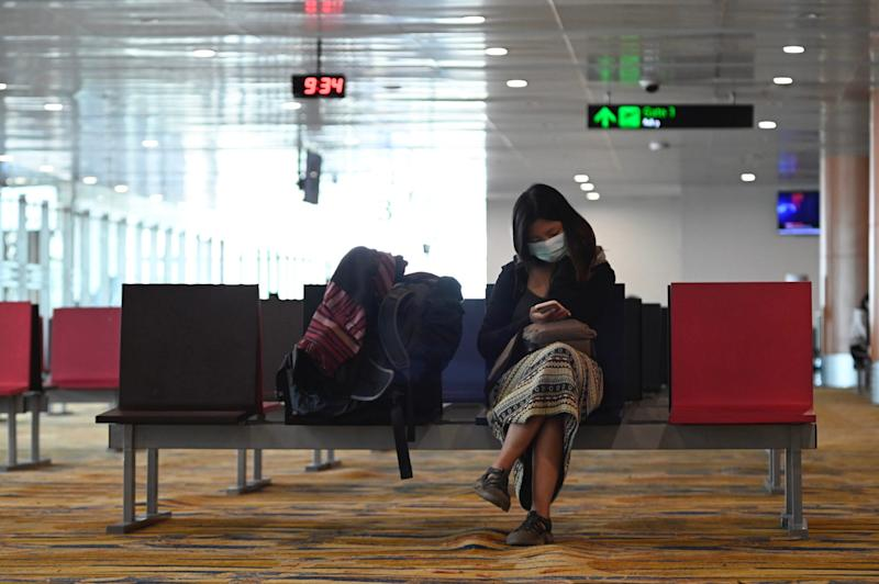 A woman wears a protective face mask at the Yangon airport on February 24, 2020. The COVID 19 coronavirus that emerged in central China at the end of last year has now killed more than 2,400 people and spread around the world. 2