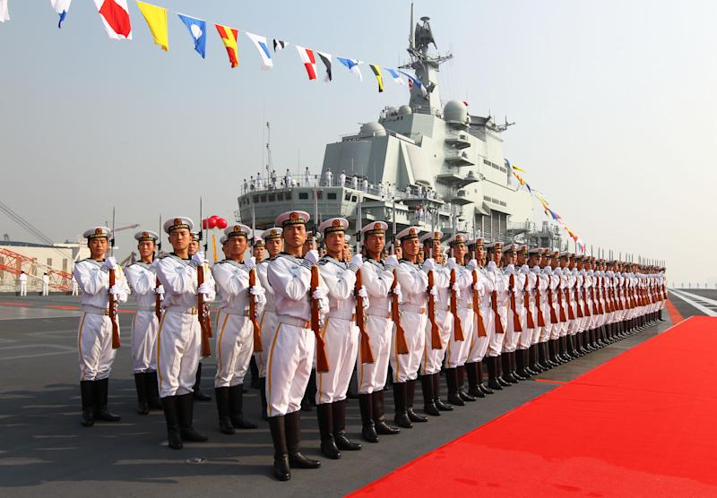 """In this photo provided by China's Xinhua News Agency, military officers stand onboard China's aircraft carrier """"Liaoning"""" in Dalian, northeast China's Liaoning Province, Tuesday, Sept. 25, 2012. China formally entered its first aircraft carrier into service on Tuesday, underscoring its ambitions to be a leading Asian naval power, although the ship is not expected to carry a full complement of planes or be ready for combat for some time. (AP Photo/Xinhua, Zha Chunming) NO SALES"""