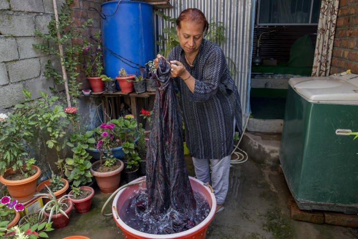 """Rinki Ahmed, a transgender Kashmiri, washes clothes at home in Srinagar, Indian controlled Kashmir, Thursday, June 3, 2021. Rinki, who worked as a model in Mumbai when younger, returned to Kashmir and became a matchmaker. """"In Kashmiri we have seen a lot of bad times due to the conflict but that never stopped me from going out. But this time nobody lets us inside their homes. I don't blame them as I am scared myself,"""" Rinki said. (AP Photo/Dar Yasin)"""