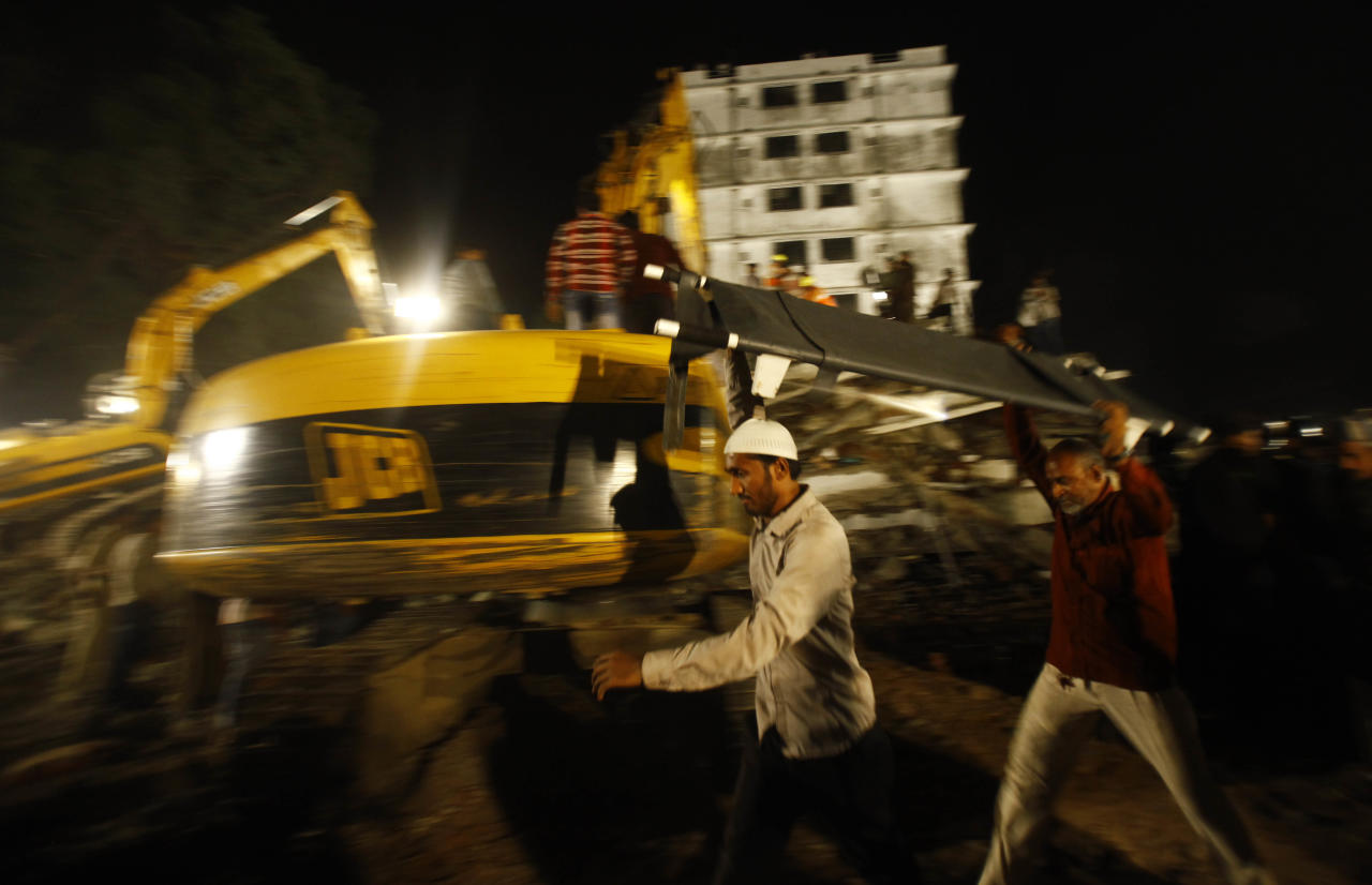 Rescue workers carry a stretcher near the site where a residential building collapsed in Thane, Mumbai, India, Thursday, April 4, 2013. At least 6 persons were killed and 40 were injured when an under construction residential building collapsed on Thursday evening according to local reports.(AP Photo/Rafiq Maqbool)