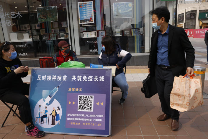 """A shopper walks past a stand offering free tickets to tourist sites as part of its campaign to encourage coronavirus vaccinations with the slogan, """"Timely vaccination to build the Great Wall of Immunity together"""" in Beijing on Friday, April 9, 2021. China's success at controlling the coronavirus outbreak has resulted in a population that has seemed almost reluctant to get vaccinated. Now, it is offering incentives — free eggs, store coupons and discounts on groceries and merchandise — to those who get a shot. (AP Photo/Ng Han Guan)"""