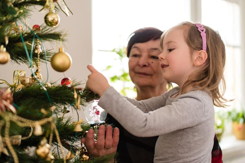 Girl child tying decorative objects on christmas tree