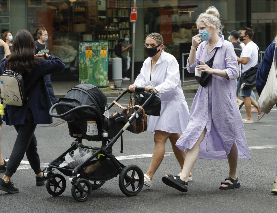 Shoppers wear masks as they walk around a shopping precinct in Sydney, Australia, Sunday, Jan. 3, 2021. Masks have been made mandatory in shopping centers, on public transport, in entertainment venues such as a cinema, and fines will come into effect on Monday as the state government responds to the COVID-19 outbreak on Sydney's northern beaches, which is suspected to have also caused new cases in neighboring Victoria state. (AP Photo/Mark Baker)
