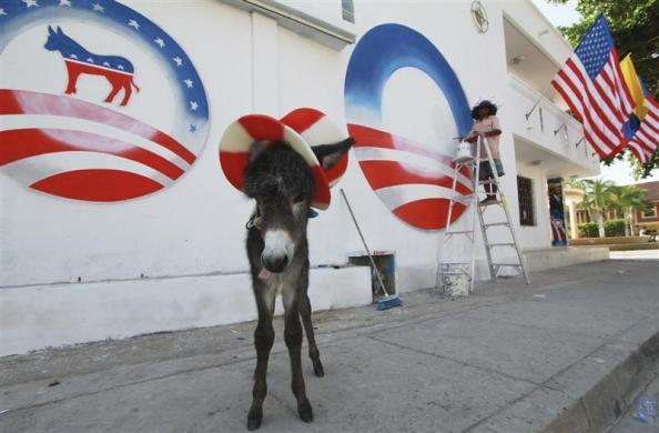 A donkey foal named Demo by owner Silvio Carrasquilla stands dressed as the mascot of the U.S. Democratic Party as a worker paints Carrasquilla's house to welcome President Obama to the VI America's Summit to be held in Cartagena, in Turbaco, near Cartagena, April 11, 2012.