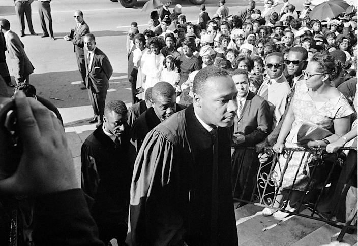 <p>Civil rights leader Rev. Dr. Martin Luther King Jr. is followed by Rev. Fred Shuttlesworth, left, and Ralph Abernathy as they attend funeral services at the Sixth Avenue Baptist Church for three of the four black girls killed in a church explosion in Birmingham, Ala., Sept. 18, 1963. (AP Photo) </p>