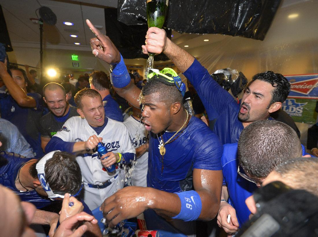 Los Angeles Dodgers players, including Yasiel Puig, pointing, celebrate in the clubhouse after they defeated the Atlanta Braves 4-3 in Game 4 of the National League baseball division series and advanced to the NL championship series, Monday, Oct. 7, 2013, in Los Angeles. (AP Photo/Mark J. Terrill)