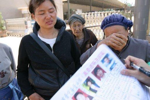 Family members display photos of their missing relatives in the village of Nanmen, southwest China