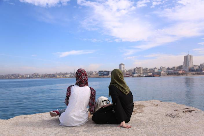 Palestinian Sara Abu Taqea, right, 23, who works in the maternity ward at Gaza's Al-Ahli hospital, and her friend spend time at the seaport last in Gaza City last November. (Photo: Samar Abo Elouf/Reuters)