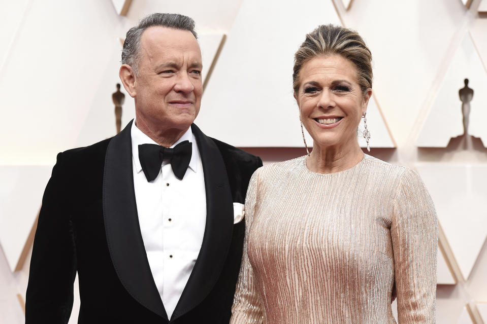 """FILE - In this Sunday, Feb. 9, 2020 file photo, Tom Hanks, left, and Rita Wilson arrive at the Oscars at the Dolby Theatre in Los Angeles. On Friday, March 13, 2020, The Associated Press reported on a manipulated image circulating online depicting actor Tom Hanks quarantined at a hospital in Australia with a volleyball that looks like Wilson, his make-believe friend in the movie """"Cast Away."""" It first circulated as satire. Hanks is in Australia shooting an Elvis Presley biopic directed by Baz Luhrmann. Hanks shared the news about his positive tests on Twitter Wednesday. (Photo by Jordan Strauss/Invision/AP)"""