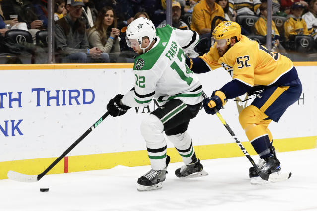 Dallas Stars center Radek Faksa (12), of the Czech Republic, moves the puck ahead of Nashville Predators defenseman Matt Irwin (52) in the first period of an NHL hockey game, Saturday, Dec. 14, 2019, in Nashville, Tenn. (AP Photo/Mark Humphrey)