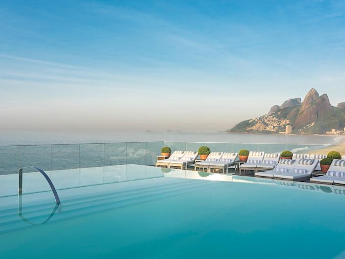 """Last but not least, an international favorite: the iconic <a href=""""https://www.cntraveler.com/hotels/brazil/lagoa/fasano-hotel-rio-de-janeiro?mbid=synd_yahoo_rss"""" rel=""""nofollow noopener"""" target=""""_blank"""" data-ylk=""""slk:Hotel Fasano in Rio de Janeiro"""" class=""""link rapid-noclick-resp"""">Hotel Fasano in Rio de Janeiro</a>. This Phillippe Starck-designed hotel features one of the sleekest, sexiest rooftop pools in the world, framed with picture-perfect views of Ipanema Beach and the Dos Irmãos mountains. Bring your best bikini—you just might run into Gisele Bündchen. International leisure travel might not be quite within reach at the moment, but that's ok—some rooftop pools are worth waiting for, and until the pandemic settles down, we'll be seeing this one in our dreams."""