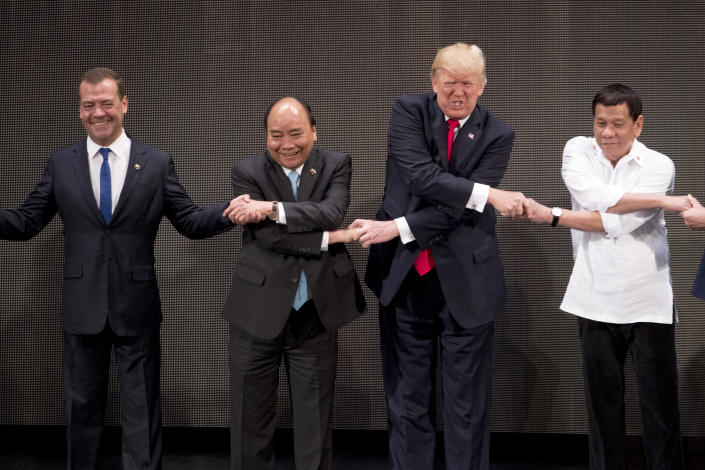 """<p>U.S. President Donald Trump, second from right, reacts as he does the """"ASEAN-way handshake"""" with Russian Prime Minister Dmitry Medvedev, left, Vietnamese Prime Minister Nguyen Xuan Phuc, second from left, and Philippine President Rodrigo Duterte on stage during the opening ceremony at the ASEAN Summit at the Cultural Center of the Philippines, Nov. 13, 2017, in Manila, Philippines. Trump initially did the handshake incorrectly. Trump is on a five-country trip through Asia traveling to Japan, South Korea, China, Vietnam and the Philippines. (Photo: Andrew Harnik/AP) </p>"""