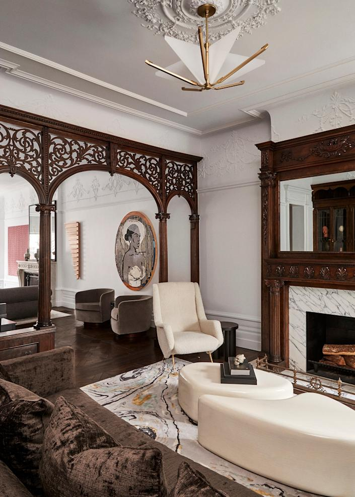 "<div class=""caption""> The library is separated from the rest of the living space by a decorative wooden archway that's original to the house, as is the fireplace with its restored Victorian mantel (the mirror now hides a television). A vintage Isa Bergamo chair upholstered in off-white shearling was paired with a resin-coated two-piece coffee table from <a href=""https://www.hollyhunt.com"" rel=""nofollow noopener"" target=""_blank"" data-ylk=""slk:Holly Hunt"" class=""link rapid-noclick-resp"">Holly Hunt</a>. Behind the archway we see a portrait by Brooklyn-based artist Mickalene Thomas and two Milo Baughman armchairs from the '70s. </div>"