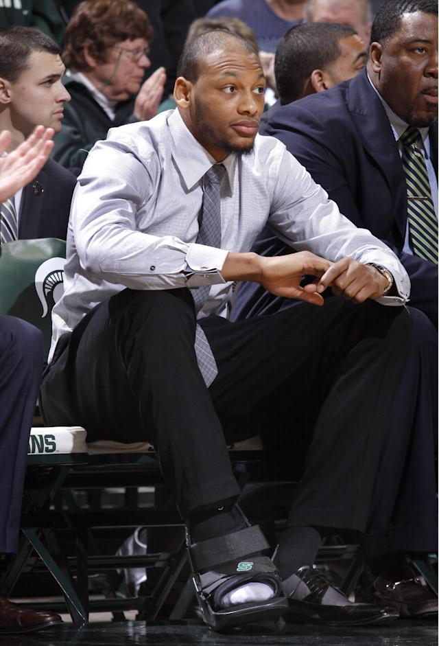 Michigan State's Adreian Payne sits on the bench in street clothes and a walking boot during the second half of an NCAA college basketball game against Michigan State, Saturday, Jan. 11, 2014, in East Lansing, Mich. Michigan State won 87-75 in overtime. (AP Photo/Al Goldis)