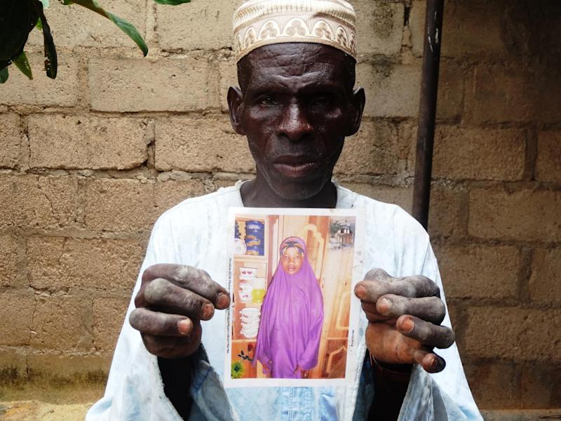 Sani Garba, 55, holds the picture of his 14-year-old daughter-in-law Wasila Tasi'u on August 10, 2014 inside her abandoned matrimonial home in the village of Unguwar Yansoro (AFP Photo/Aminu Abubakar)