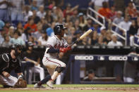Atlanta Braves' Ozzie Albies, right, hits a double during the eighth inning of a baseball game against the Miami Marlins, Saturday, Aug. 10, 2019, in Miami. (AP Photo/Brynn Anderson)