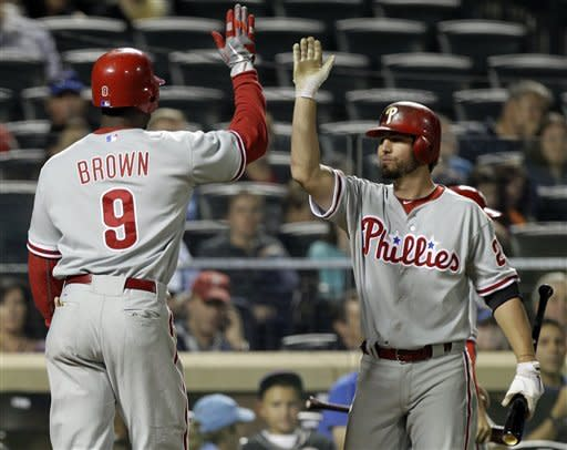 Philadelphia Phillies' Kevin Frandsen, the on-deck batter, greets teammate Domonic Brown (9) after Brown's seventh-inning solo home run in the Phillies baseball game against the New York Mets at Citi Field in New York, Monday, Sept. 17, 2012. (AP Photo/Kathy Willens)