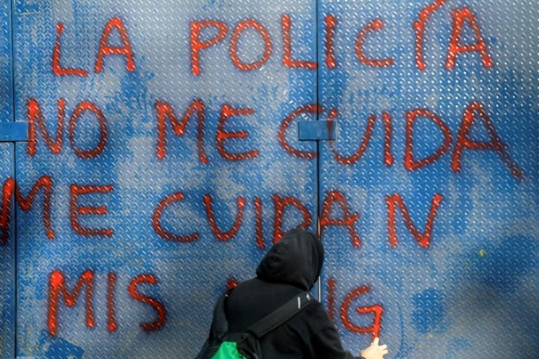 "A woman writes ""Police don't take care of me"" on a wall during a demonstration in the Mexican capital"