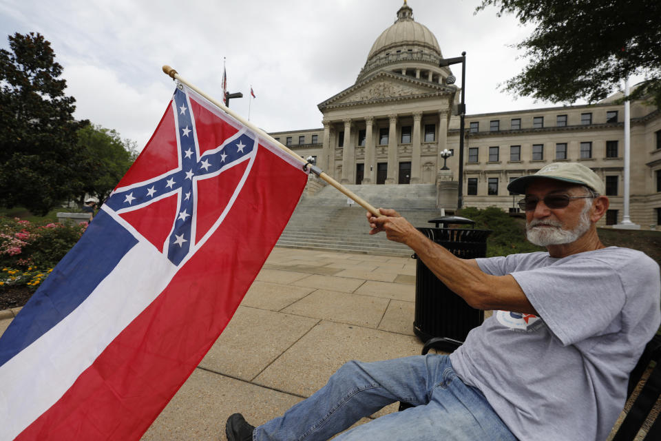 Larry Eubanks of Star waves the current Mississippi state flag as he sits before the front of the Capitol, Saturday, June 27, 2020, in Jackson, Miss. While a supporter of the current flag, Eubanks says he would hope lawmakers would allow a proposed flag change to be decided by the registered voters. The current state flag has in the canton portion of the banner the design of the Civil War-era Confederate battle flag, that has been the center of a long-simmering debate about its removal or replacement. (AP Photo/Rogelio V. Solis)