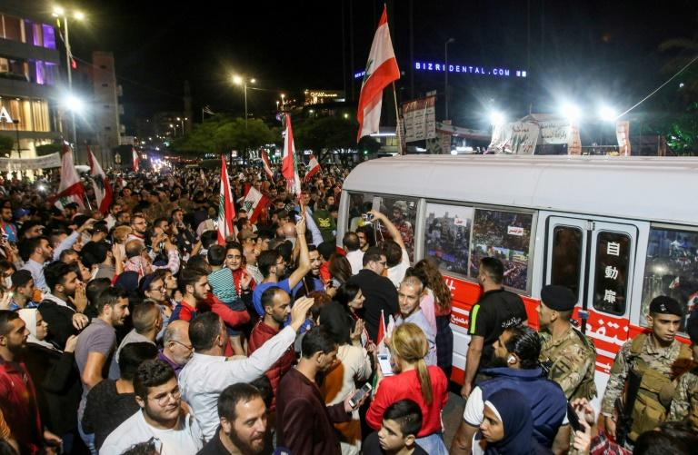 "A ""revolution"" bus carrying Lebanese anti-government protesters on a cross-country trip from the north to the south is met in the southern city of Sidon on November 16, 2019"