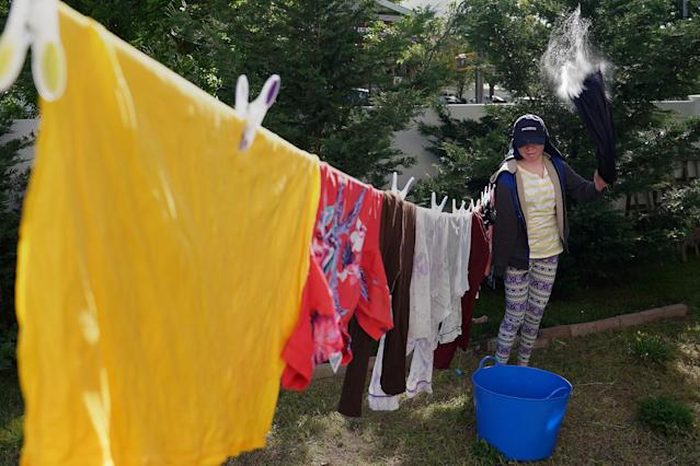 <p>Pendo Noni, 16, a Tanzanian with albinism who had an arm chopped off in a witchcraft-driven attack, shakes the water out of her clothes as she does laundry at the Global Medical Relief Fund house in the Staten Island borough of New York City, June 2, 2017. (Photo: Carlo Allegri/Reuters) </p>