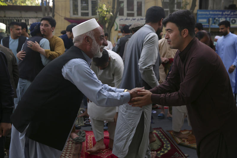 Afghan Muslims greet each other after offering Eid al-Adha prayers in Kabul, Afghanistan, Friday, July 31, 2020. During the Eid al-Adha, or Feast of Sacrifice, Muslims slaughter sheep or cattle and distribute portions of the meat to the poor. (AP Photo/Rahmat Gul)