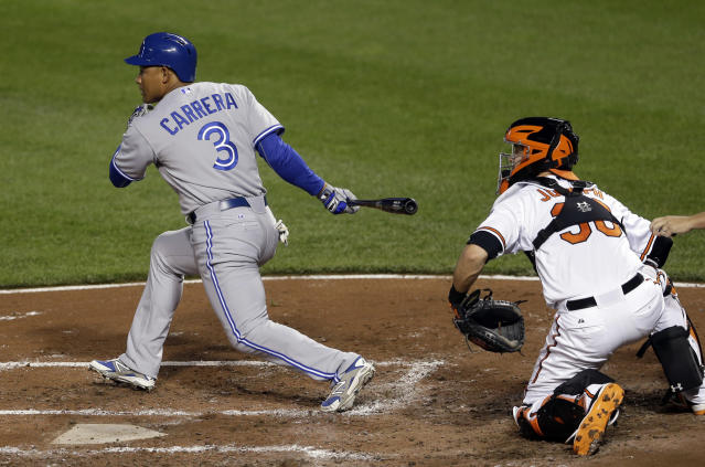 Toronto Blue Jays' Ezequiel Carrera, left, doubles in front of Baltimore Orioles catcher Caleb Joseph in the fifth inning of a baseball game, Monday, May 11, 2015, in Baltimore. Kevin Pillar scored on the play. (AP Photo/Patrick Semansky)