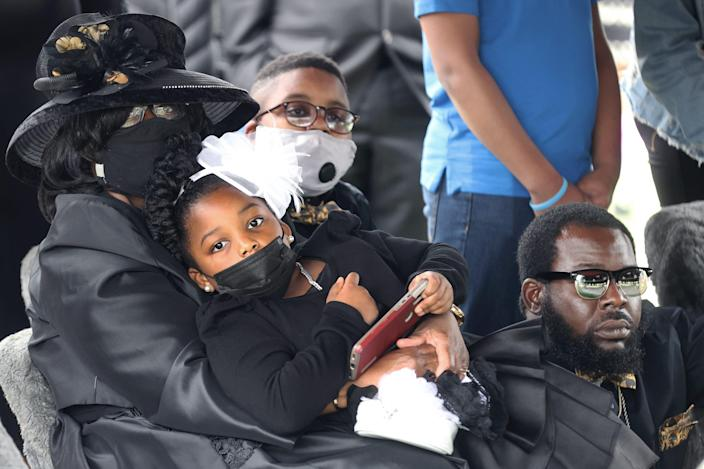 Widow Cathy Beck holds her grandchildren Ivy Monroe, 7, and R.J. Miller, 11, with son Ivory Beck Jr., right, by her side as they watch the honor guard fold the flag of Ivory Beck Sr. during funeral services at Memorial Park South Woods on May 29, 2021.