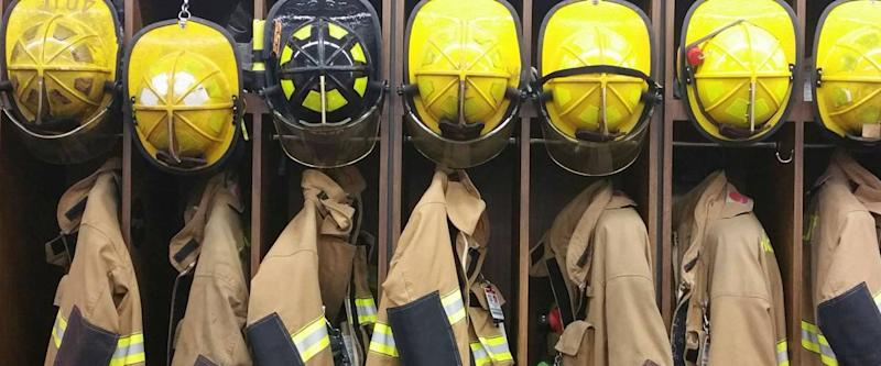 A lineup of firemen's helmets and turnout gear in a locker at a volunteer fireman's station