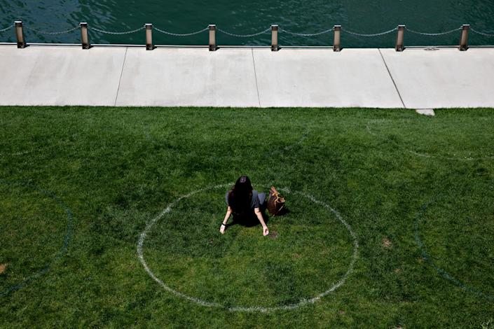 A woman sits in a social distance circle along the Chicago River in Chicago, on Aug. 4, 2020.   Daniel Acker/The New York Times–Redux