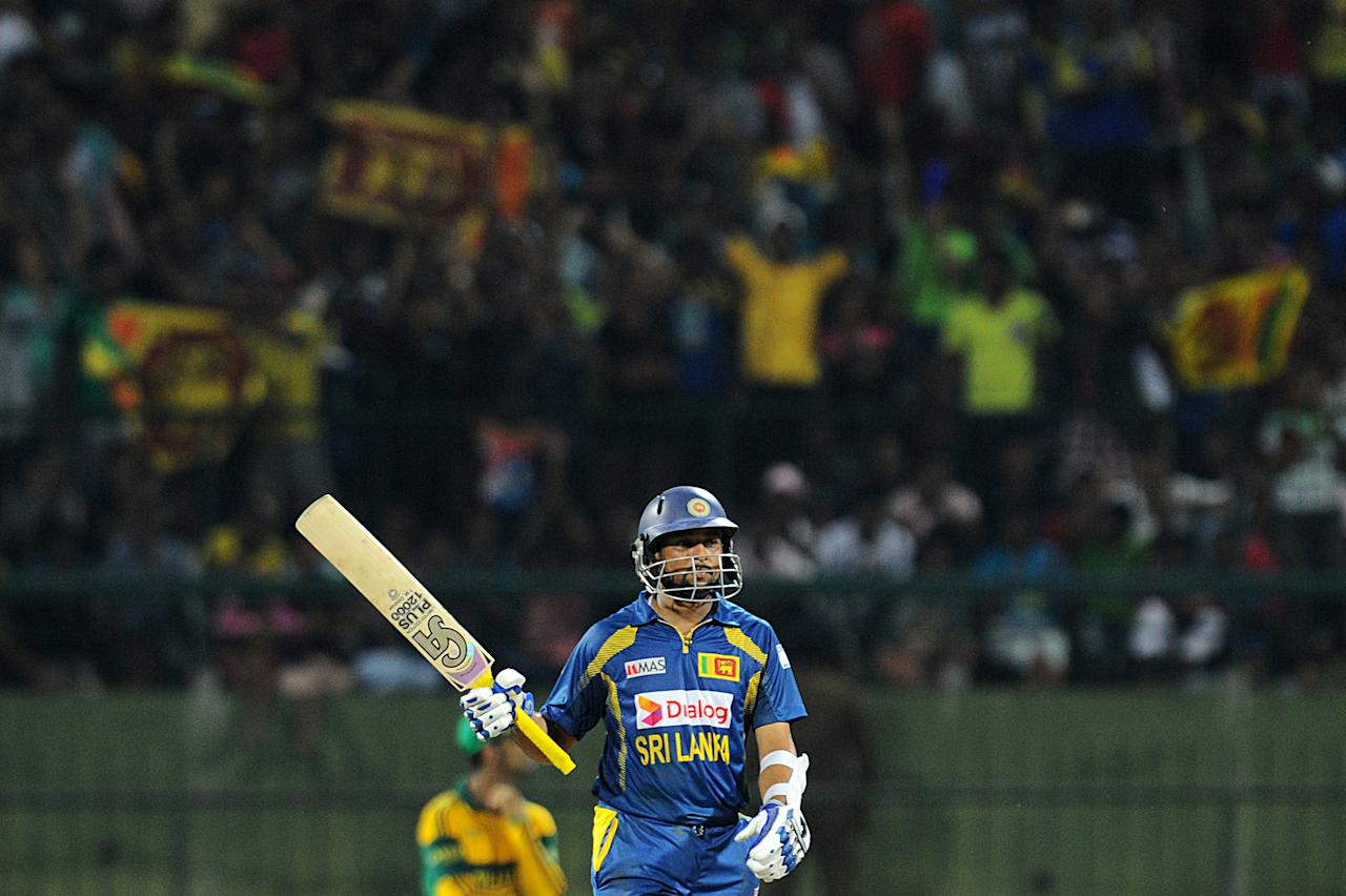 Sri Lankan batsman Tillakaratne Dilshan raises his bat to the crowd after scoring a half-century (50 runs) during the fourth One Day International (ODI) cricket match between Sri Lanka and South Africa at the Pallekele International Cricket Stadium in Pallekele on July 28, 2013. AFP PHOTO/ Ishara S.KODIKARA