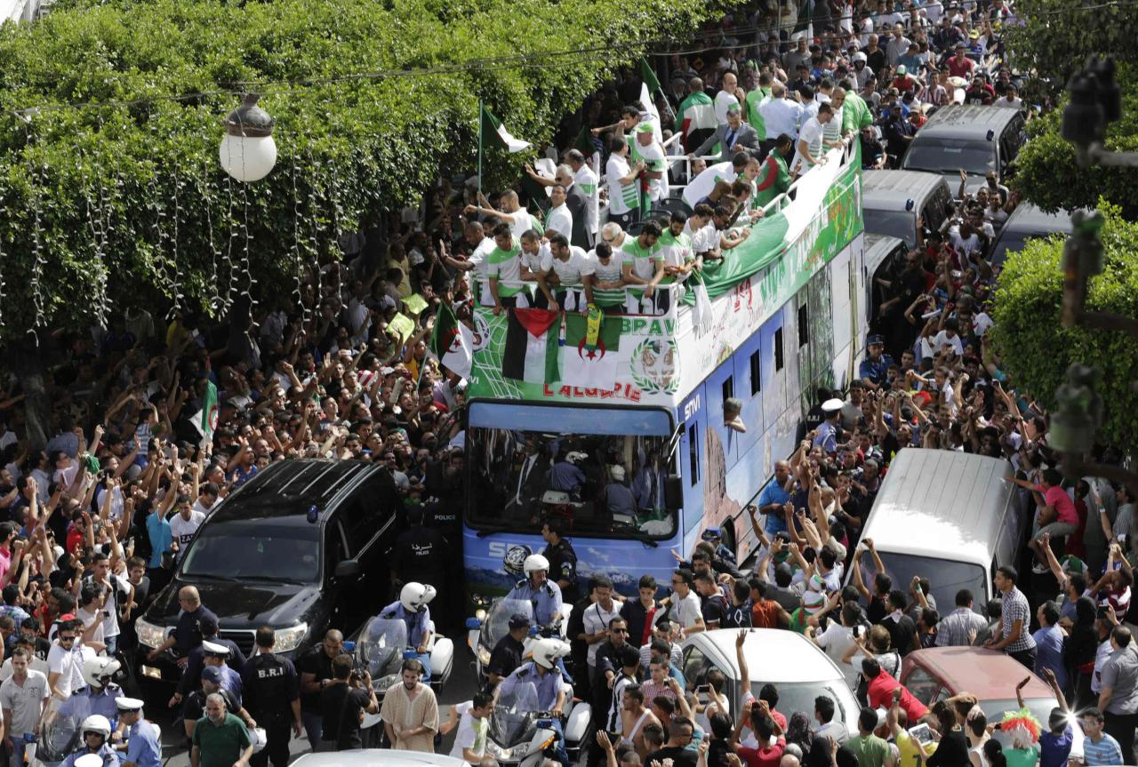 Algeria's soccer players (on bus) are welcomed by fans in downtown Algiers, after returning from the 2014 World Cup soccer tournament, July 2, 2014. Algeria was knocked out from the World Cup by Germany after reaching the round of 16 for the first time. REUTERS/Louafi Larbi (ALGERIA - Tags: SPORT SOCCER WORLD CUP)