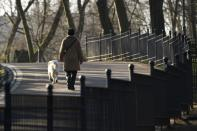 A woman walks with her dog at the Volkspark Friedrichshain in Berlin