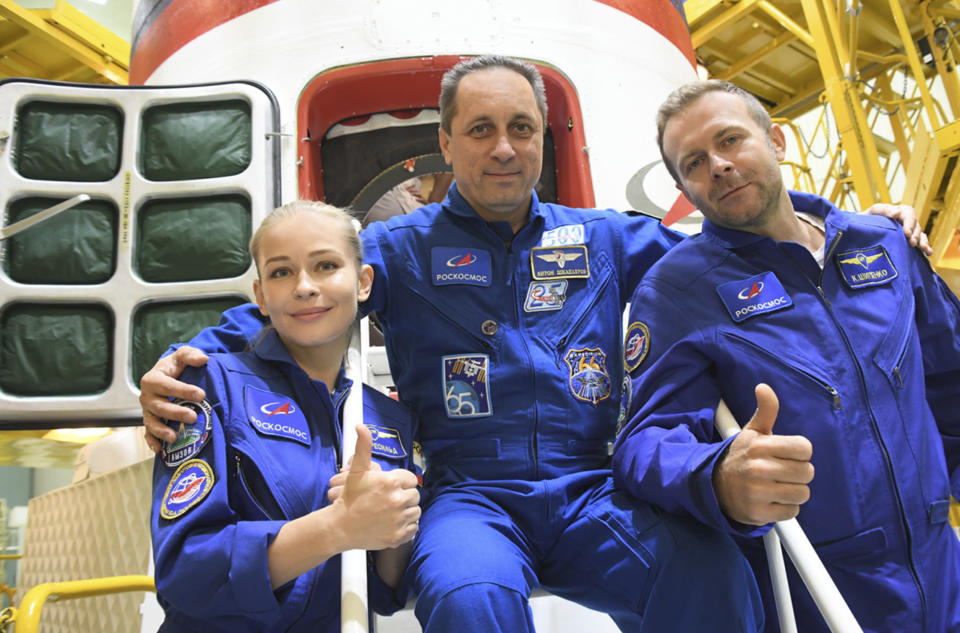 In this handout photo released by Roscosmos, Actress Yulia Peresild, left, director Klim Shipenko' right, and cosmonaut Anton Shkaplerov, members of the prime crew of Soyuz MS-19 spaceship pose at the Russian launch facility in the Baikonur Cosmodrome, Kazakhstan, Wednesday, Sept. 29, 2021. In a historic first, Russia is set to launch an actress and a film director to space to make a feature film in orbit. Actress Yulia Peresild and director Klim Shipenko are set to blast off Tuesday for the International Space Station in a Russian Soyuz spacecraft together with Anton Shkaplerov, a veteran of three space missions. (Roscosmos Space Agency via AP)