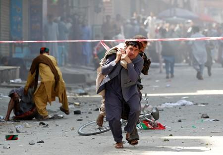 A man caries a wounded person to the hospital after a blast in Jalalabad
