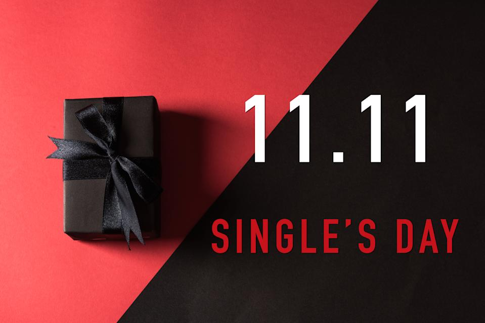 11:11 sale shopping concept, Top view of gift box wrapped in black paper and black bow ribbon with 11.11 single's day text at side space, studio shot on red and dark background