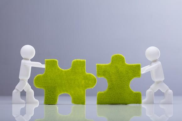 Miniature figures pushing green jigsaw puzzle pieces together