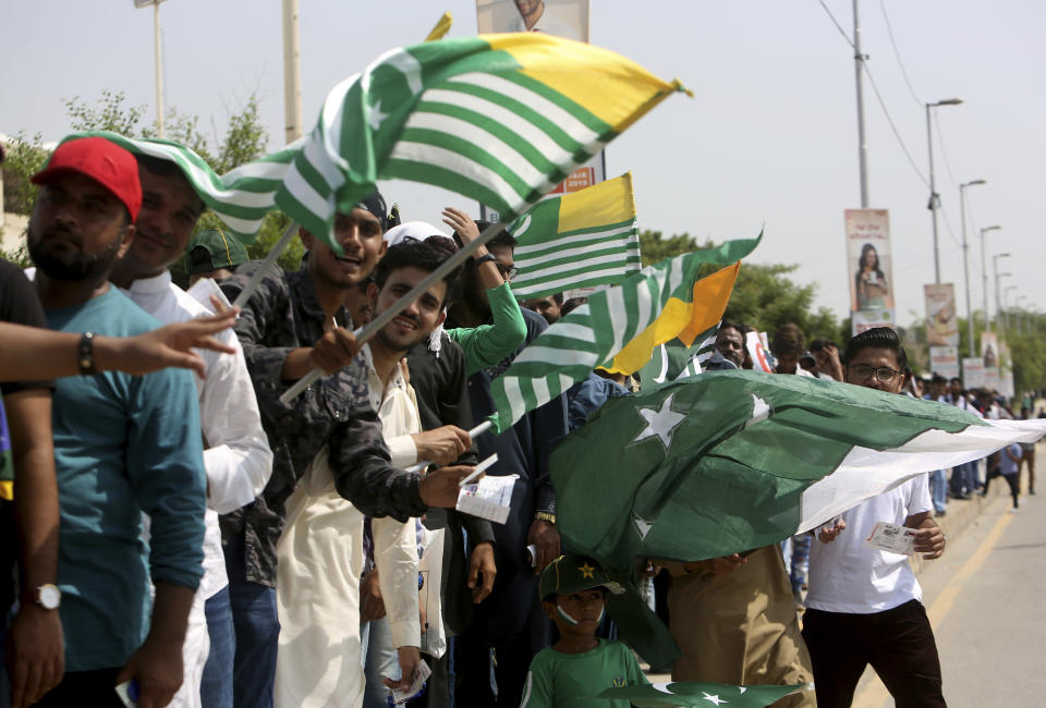 Pakistani cricket fans wave Kashmiri flags to express solidarity with Indian Kashmiris, as they wait to enter the National stadium in Karachi, Pakistan, Monday, Sept. 30, 2019. Karachi's 10-year long wait to host a one-day international finally ended on Monday as Pakistan won the toss and elected to bat against Sri Lanka in the second ODI. (AP Photo/Fareed Khan)