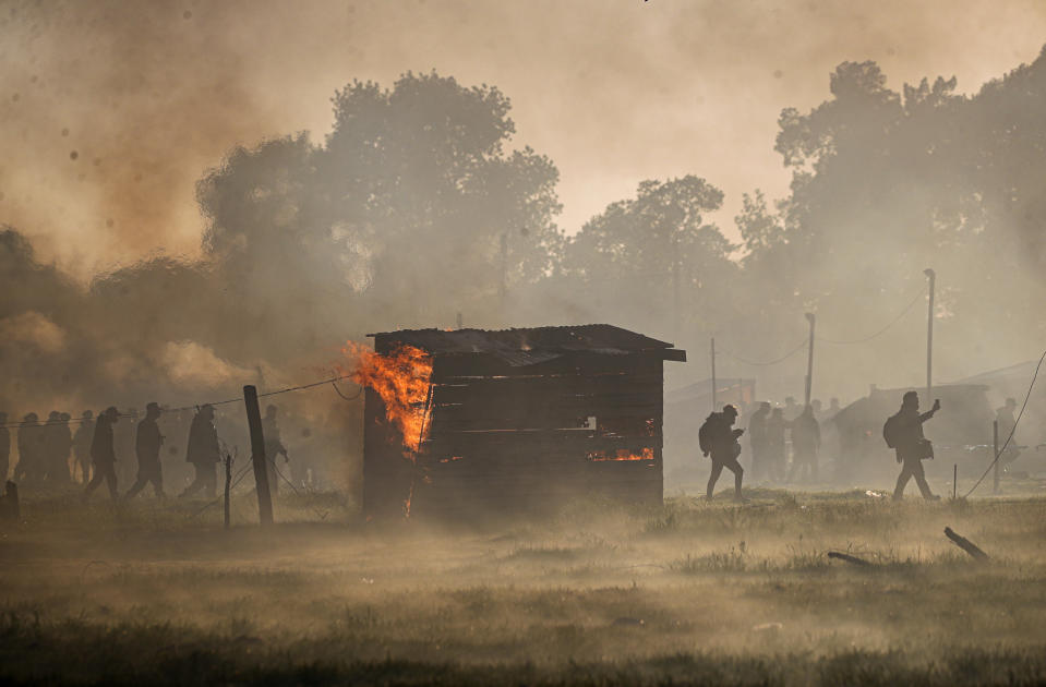 Police carry out an eviction at a squatters camp where a shack home burns in Guernica, Buenos Aires province, Argentina, Thursday, Oct. 29, 2020. A court ordered the eviction of families who are squatting here since July, but the families say they have nowhere to go amid the COVID-19 pandemic. (AP Photo/Natacha Pisarenko)