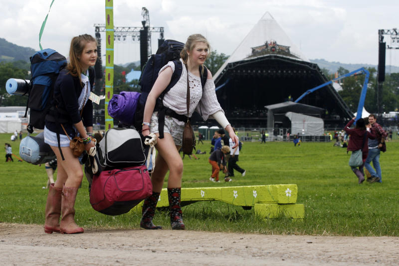 Festival goers arrive at the Glastonbury Music Festival site, Glastonbury, England on Wednesday, June 26, 2013. Thousands are to arrive for the three day festival that starts on Friday, June 28 with headliners, Arctic Monkeys, the Rolling Stones and Mumford and Sons. (Photo by Jim Ross/Invision/AP)